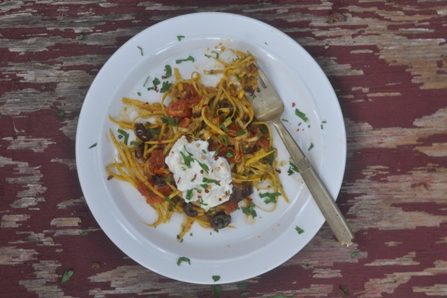 zucchini pasta with pesto, tomatoes, and olives